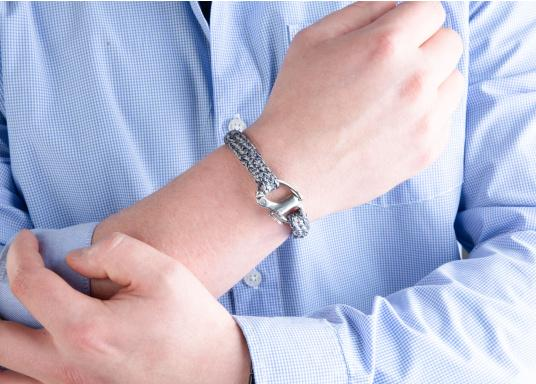 "The ""Bugspriet"" wristband from Gemma Spartum is made of sailing rope and features an elegant mottled design with a discreet stainless steel emblem. A charming paring of robust sailing rope and elegant arm jewellery. It can be worn on any occasion as its colour tone is not obtrusive. It includes a snap shackle similar to links used in sailing, a real eye-catcher. (Imagen 4 of 4)"